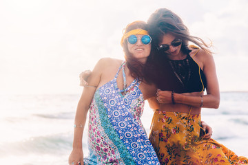 Boho girls walking on the beach