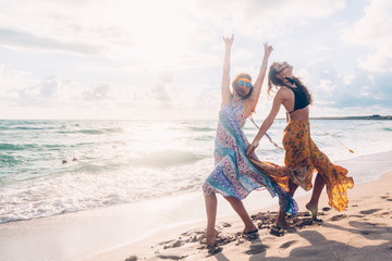 Boho girls walking on the beach