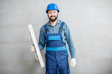 Portrait of a handsome builder in blue working uniform plastering the wall indoors Wall mural