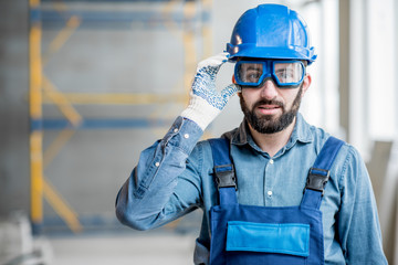 Close-up portrait of a handsome bearded builder with protective glasses and helmet indoors Wall mural