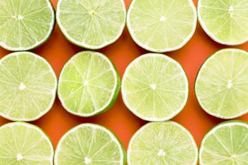 Lime split in half on an orange background