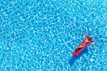 Slim young woman lying on air mattress in the pool
