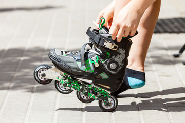 Young woman putting roller skates on
