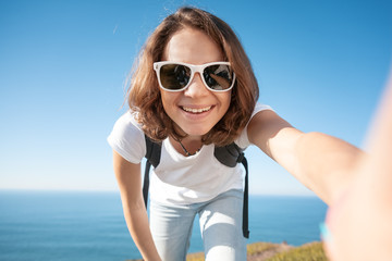 Young attractive funny girl in a white T-shirt and jeans against the blue sea and sky, makes selfie, summer travel and adventure, vacation concept