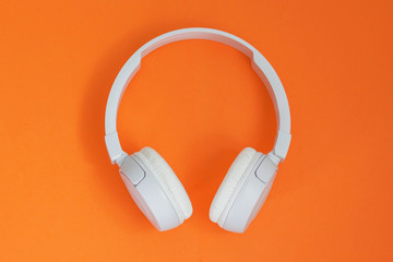 Headphone. Music concept. Flat lay: headphones on orange background. Top view. Trendy colorful photo.