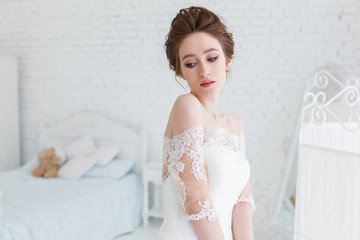 Bride posing in wedding dress in the studio on a background of a brick wall and white bed. Horizontal close portrait
