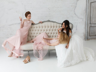 brides taking selfie while playing on sofa and drinking champagne
