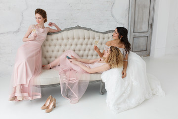 brides talking and playing on sofa and drinking champagne. Morning preparation for wedding ceremony