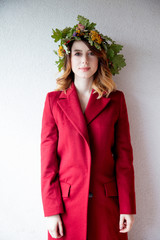 young redhead girl with oak leaves wreath in red coat on white wall background