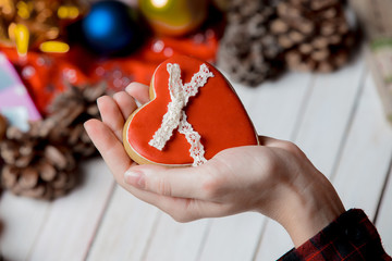 Female holding a heart shape cookie on wooden white background with gifts around.