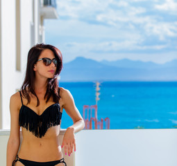 Girl in sunglasses and black bikini in hotel near sea in Greece