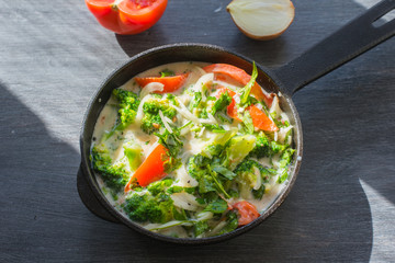 Mixed raw eggs, broccoli and tomatoes and vegetables in a frying pan - cooking omelette tomatoes