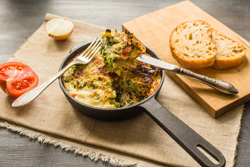 Traditional Italian omelette with broccoli and tomatoes in a frying pan on a rustic background