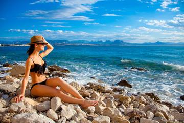 Youg girl in bikini sitting on beach near a sea in Greece