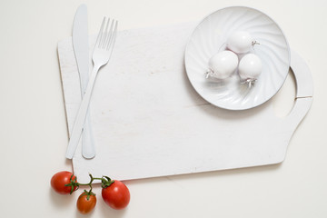 Bunch of tomatoes stock images. White fork knife plate on an old wooden plank tray. Art idea white tomatoes, painted with paint. Bright spot three red tomatoes. Fresh red tomatoes