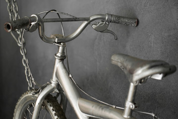 Silver bike hanging on chains against the wall in the Studio