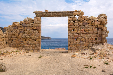 The ruins of an ancient building in the picturesque village of Firopotamos on Milos Island. Cyclades, Greece.