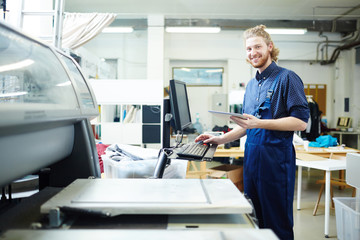 Portrait of man doing orders of his clients on printing machine