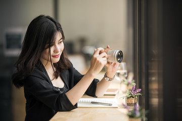 Beautiful woman in black suite holding camera and looking at screen while working at cafe