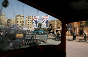 Posters of Egypt's President Sisi are seen from the broken glass of car during preparations for the presidential election in Cairo