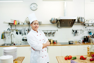Young professional chef in uniform with crossed arms looking at camera in the kitchen