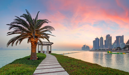 Doha with palm at dramatic sunset, Qatar