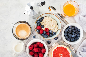 Healthy breakfast table with oatmeal porridge,  fresh berries and coffee