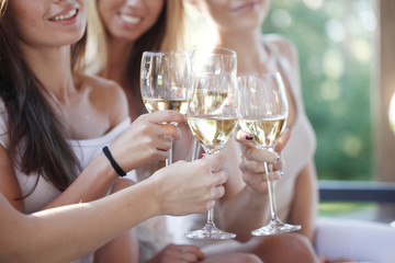 Happy friends toasting wine