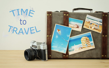 Image of old vintage luggage with vacation photos over wooden floor.