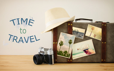 Wall Mural - Image of old vintage luggage with vacation photos over wooden floor.