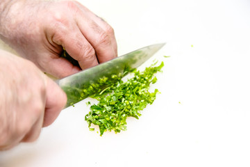 Cook cuts parsley on a white Board