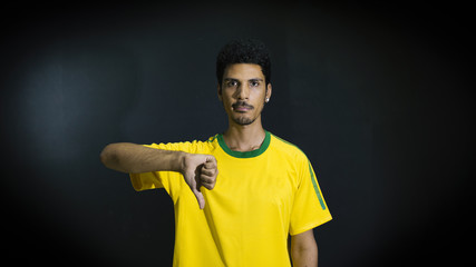 Male athlete or fan in yellow uniform with thumb down on black background