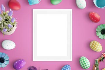 Picure frame mockup on pink desk. Easter decorations beside. Flat lay.
