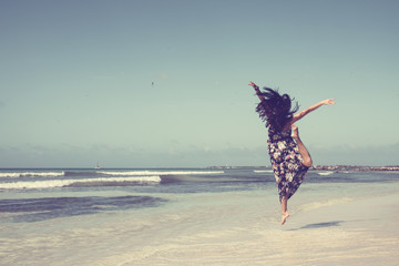 Girl jumping on the beach. Lifestyle conception.