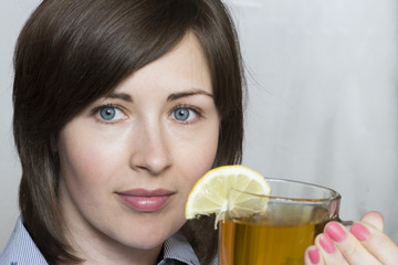 A girl is drinking tea with a lemon. A sweet drink. Neutral background. Front view. Close-up.