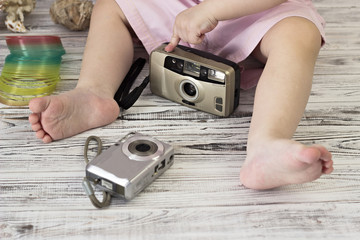 Little girl is playing with two cameras