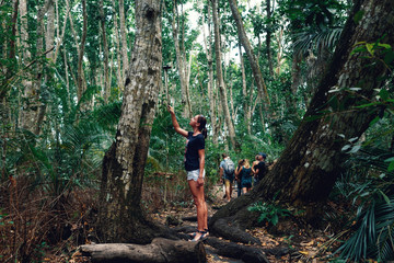 Woman tourist photographing herself in dense tropical forest