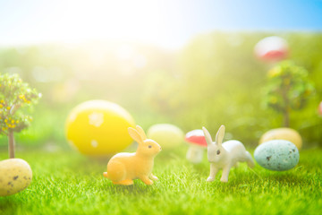 Happy Easter concept. Easter rabbits toy on spring green grass. Fairy tale sunset on the plastic green field with plastic grass, mushrooms and trees. Fake grass. Macro