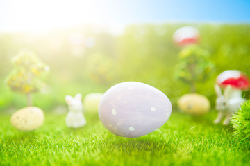 Happy Easter concept. Baby Easter bunny on spring green grass. Fairy tale sunset on the plastic green field with plastic grass, mushrooms and trees. Fake grass. Macro