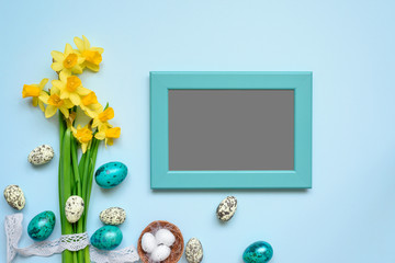 blank photo frame with easter eggs and spring flowers mock up over blue background. top view