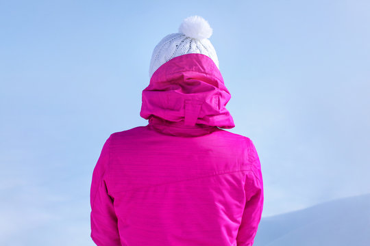 Detail view from back to young woman in pink ski jacket standing on top of the mountain.