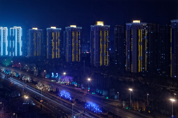 Illuminated skyscraper build in a row and a motorway by night, Shenyang, China