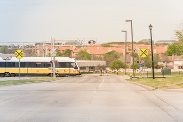 Light rail train speeding through a red alert sign level crossing in downtown Las Colinas, Irving, Texas, USA. Railway line intersection with barrier gate closing