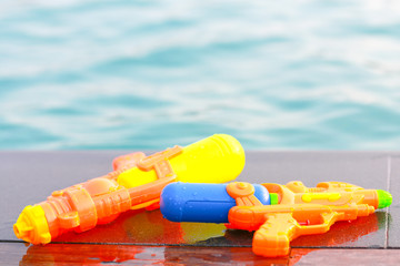 Water guns nearby the swimming pool.