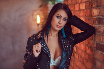 Portrait of a sexy sensual brunette posing in underwear and stylish leather jacket leaning against a brick wall.