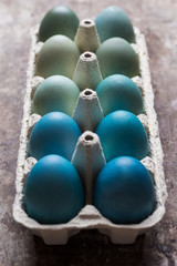 Happy Easter rustic concept. DIY dyed various shades of blue Easter eggs on retro rusty metal background.