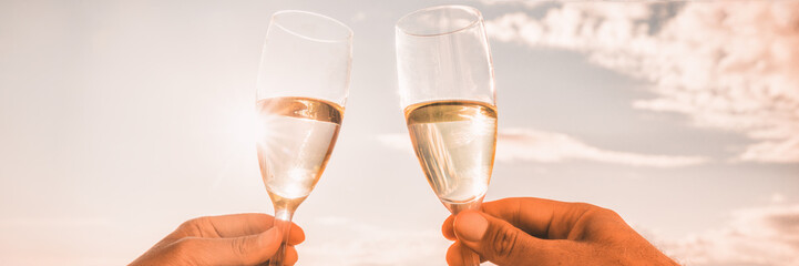 Couple toasting wine glasses for celebration. Champagne toast in luxury restaurant. Two people holding flutes doing cheers. Banner panorama crop on sunset background.