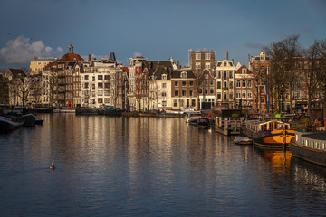 water canals in Amsterdam with  traditional architecture reflecting in the water on a sunny day