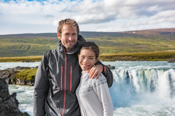 Wall Mural - Iceland tourists couple portrait in famous touristic attractionn. People smiling posing in front of Godafoss waterfall, Europe summer travel young travelers.