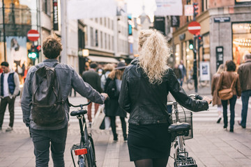 Couple walking with city bikes in Copenhagen street shopping. Urban living lifestyle. Commuting with bicycle, young students couple tourists traveling in Europe.